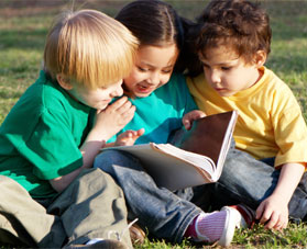 three kids reading a book outdoors